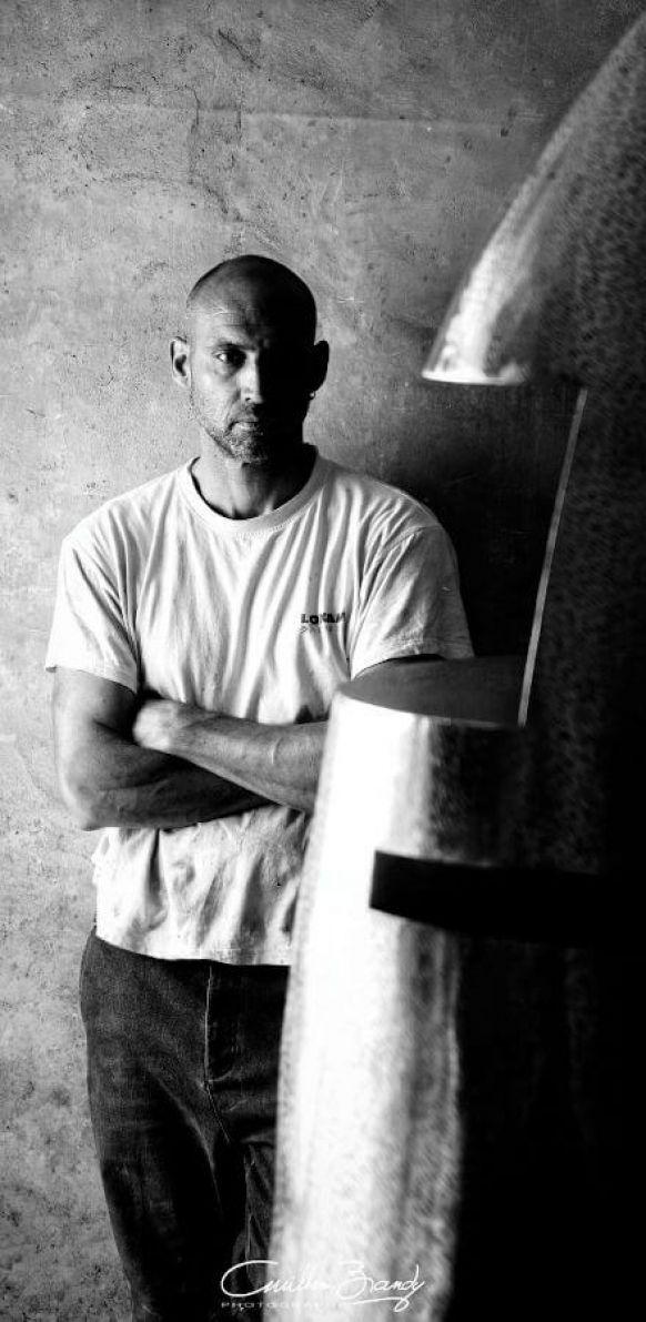 Portrait de Félix Valdelièvre, sculpteur métal, dans son atelier avec en premier plan une sculpture inox de 2m intitulée Tavelée